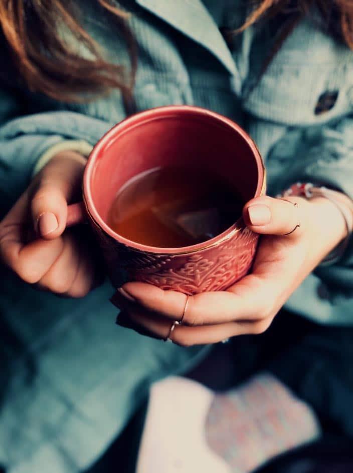 tasse de thé tenue entre ses mains lors d'un moment cocooning